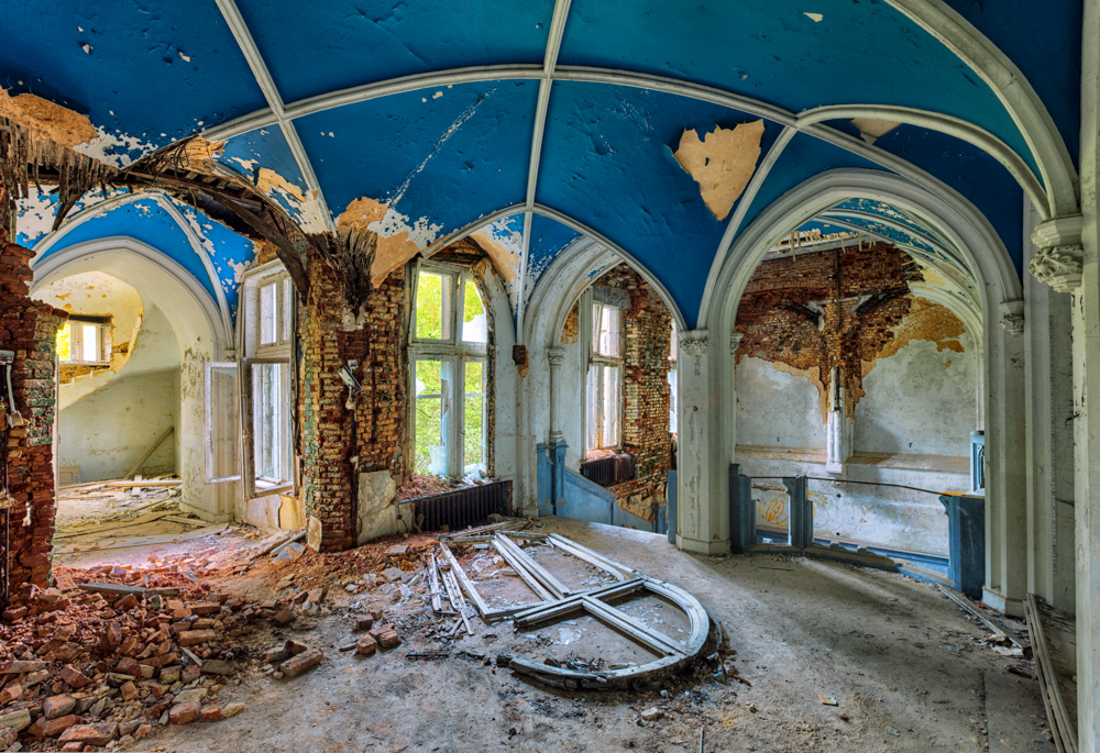 decay room in castle with arch and broken window