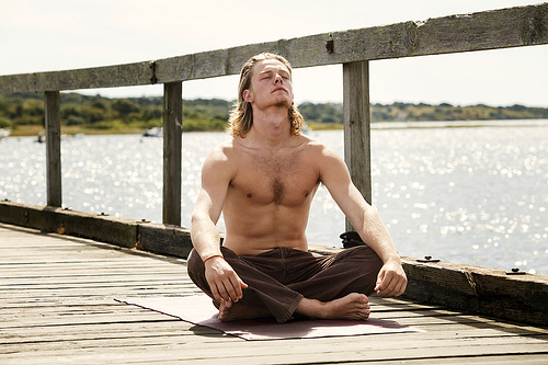 Young Man Doing Yoga on Pier
